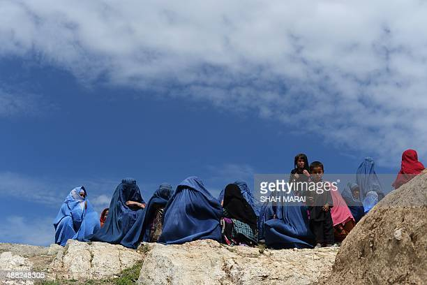 Afghan villagers sit together near the scene in the landslidehit Aab Bareek village in Argo district of Badakhshan on May 5 2014 Rescue teams...