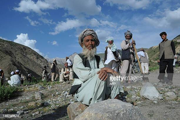 Afghan villagers take a break during a search for victims following an earthquake in a village at Burka district the worsthit area in the province of...