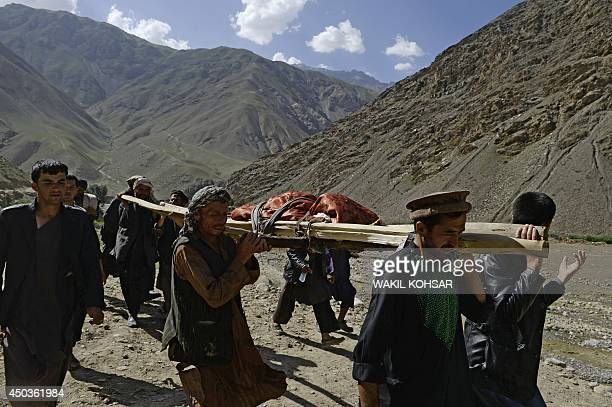 Afghan villagers transport the body of a resident killed in a landslide following flooding in the GuzargaheNur district of Baghlan province on June 9...