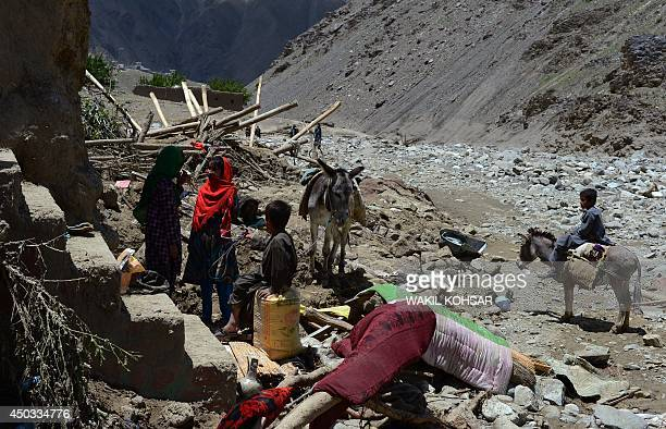 Afghan villagers wait to load belongings on to a donkey in an area affected by flooding in the GuzargaheNur district of Baghlan province on June 9...