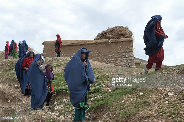 Afghan villagers walk near the scene in the landslidehit Aab Bareek village in Argo district of Badakhshan on May 5 2014 Rescue teams abandoned the...