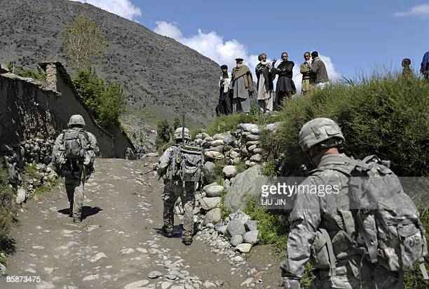 Afghan villagers watch US soldiers from 1st Infantry Division patrolling through the town of Naray, in Afghanistan's eastern Kunar province, on April...