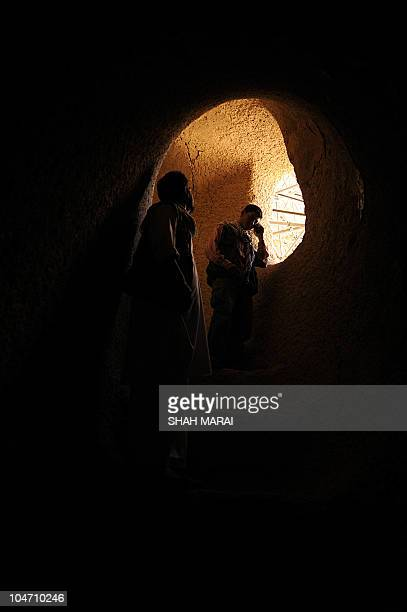 Afghan visitors stand and look inside the empty seat of the Buddha which was destroyed by the Taliban in Bamiyan on July 7 2008 at the...