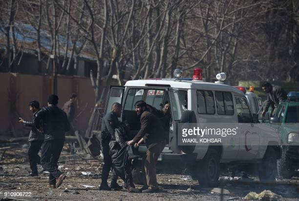 Afghan volunteers and policemen carry injured men on an ambulance at the scene of a car bomb exploded in front of the old Ministry of Interior...