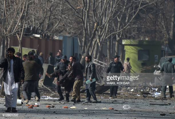 TOPSHOT Afghan volunteers and policemen help wounded at the scene of a car bomb exploded in front of the old Interior Ministry building in Kabul on...