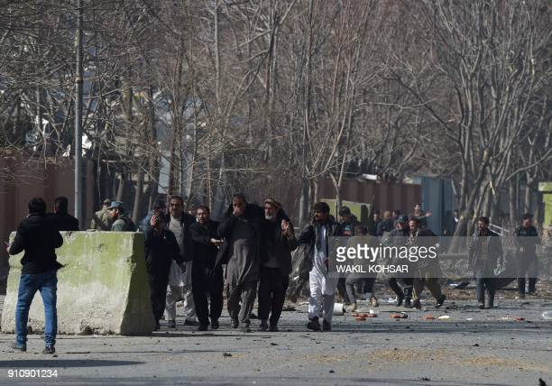 Afghan volunteers and policemen help wounded at the scene of a car bomb exploded in front of the old Interior Ministry building in Kabul on January...