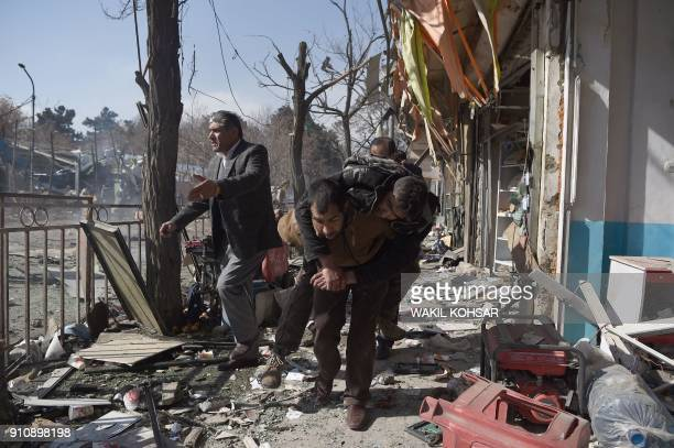 TOPSHOT Afghan volunteers carry a body at the scene of a car bomb exploded in front of the old Ministry of Interior building in Kabul on January 27...