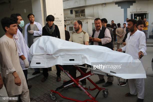 Afghan volunteers carry a dead body on a stretcher to a hospital following a suicide attack in Kabul on August 15 2018 At least 37 people the...
