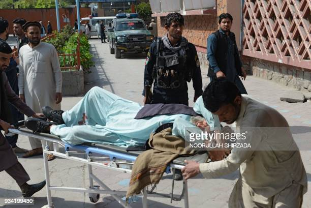 Afghan volunteers carry an injured man on a stretcher to a hospital following a bomb blast in Jalalabad on March 19 2018 A bombrigged motorbike...