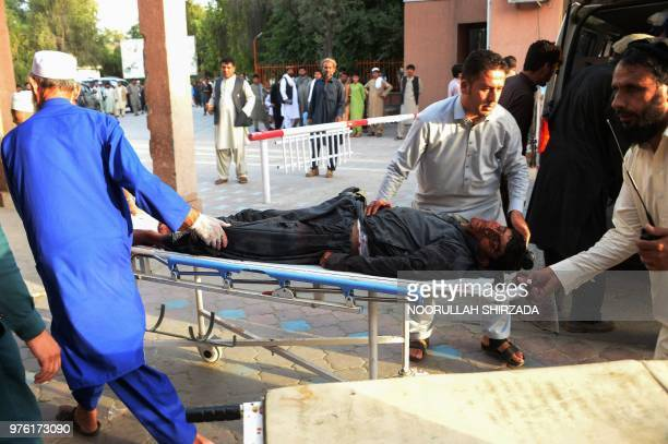 Afghan volunteers carry an injured man on a stretcher to an hospital following a suicide bomber blew himself in Jalalabad on June 16 2018 A suicide...
