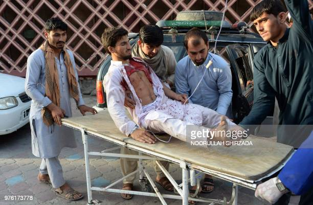 TOPSHOT Afghan volunteers carry an injured man on a stretcher to an hospital following a suicide bomber blew himself in Jalalabad on June 16 2018 A...