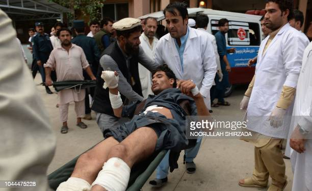 Afghan volunteers carry an injured youth on a stretcher to a hospital following an attack that targeted a parliamentary election rally in the Kama...
