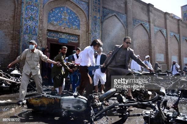 Afghan volunteers carry victims at the scene of a motorcycle bomb explosion in front of the Jami Mosque in Herat on June 6 2017 A motorcycle bomb...