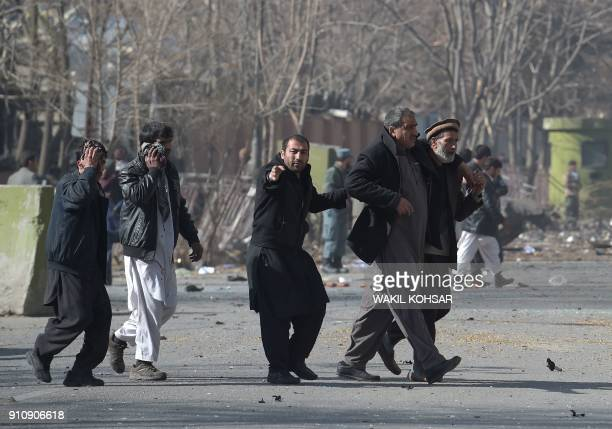 Afghan volunteers help an injured men at the scene of a car bomb exploded in front of the old Ministry of Interior building in Kabul on January 27...