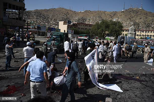 Afghan volunteers move the bodies of victims at the scene of a suicide attack that targeted crowds of minority Shiite Hazaras during a demonstration...