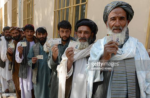 Afghan voters display their national identity cards as they queue to cast their votes at a local polling station in Kandahar on April 5 2014 Afghan...