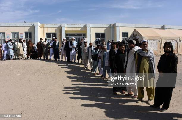 Afghan voters wait in line to cast their votes at a polling centre for the country's legislative election in Kandahar on October 27 2018 Afghans...