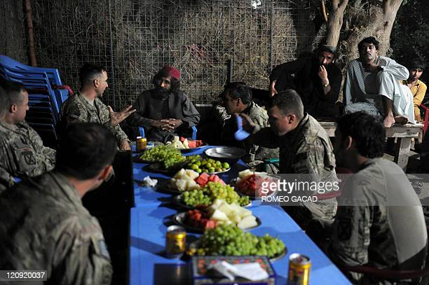 Afghan warlord Haji Tor Gani wearing a red cap hosts an iftar reception for US military officials belonging to 2nd Battalion 87th Infantry Regiment...