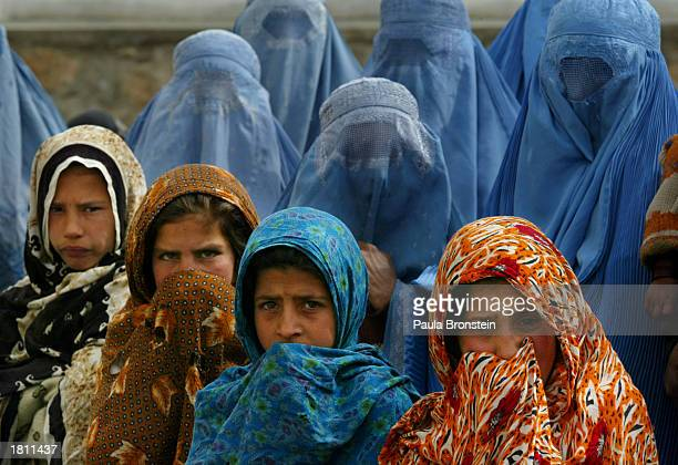 Afghan women and girls wait in line to be treated at the Kalakan health clinic February 232003 in Kalakan Afghanistan