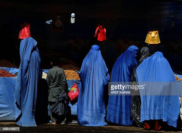 Afghan women buy fruit at the one of the main markets in Herat on October 1 2014 Muslims across the world are preparing to celebrate the annual...