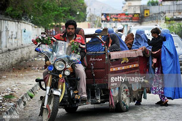 Afghan women clamber onto an autorickshaw as they leave a polling station in Jalalabad on April 5 2014 Afghan voters went to the polls to choose a...