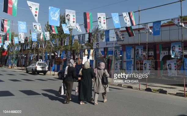 Afghan women cross a road as posters of candidate Ahamd Tamin Jurat are installed during the parliamentary election campaign in Kabul on October 2...