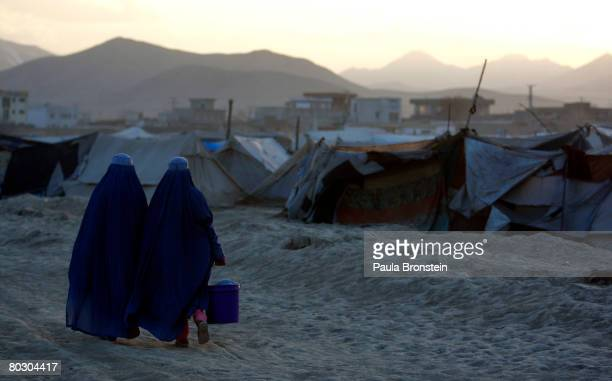 Afghan women from the southern province of Helmand walk to their tents on March 16, 2008 in Kabul, Afghanistan. There are 165 families living in...