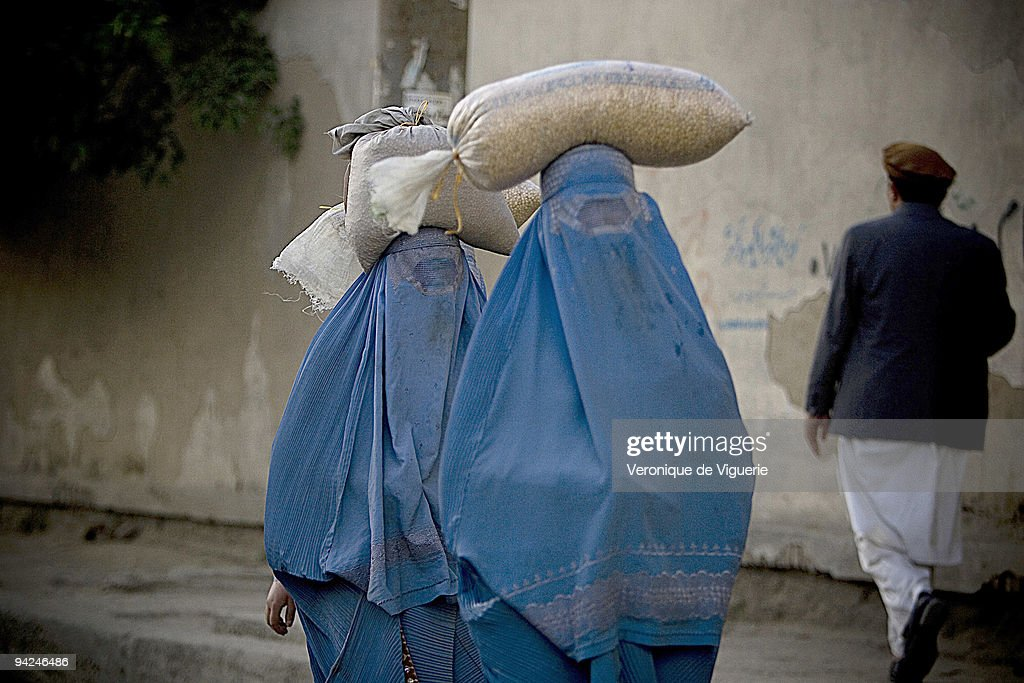 Afghan women have to wear the burqa once they have passed puberty, as pictured here in the streets of Kabul, carrying bags of food on their heads.