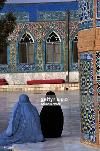 Afghan women in burqas pass by one of the best known mosques in the Muslim world in Mazar-e-Sharif, northern Afghanistan