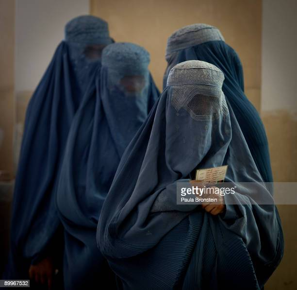 Afghan women in burqas wait in line at a polling station on August 20, 2009 in Kabul, Afghanistan. Afghans voted on Thursday to elect a president for...