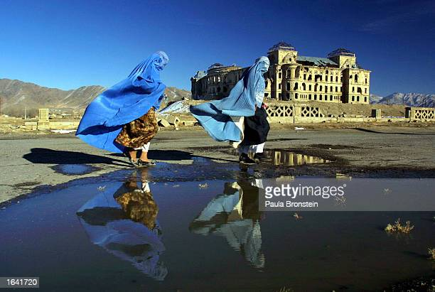 Afghan women in burqas walk on a breezy winter day in front of the Darulaman Palace February 3 2002 in Kabul Afghanistan The palace was once the...