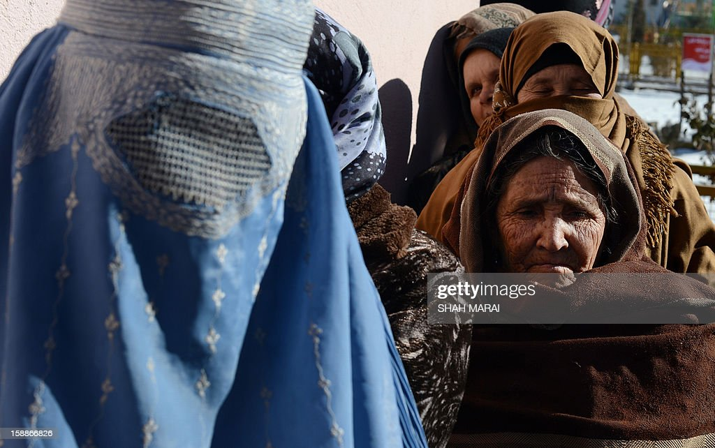 Afghan women line up to receive winter supplies at a UNHCR distribution centre for needy refugees at the Women's Garden in Kabul on January 2, 2013. Hundreds of families living in makeshift shelters around the Afghan capital Kabul collected blankets, charcoal and other supplies on January 2 as authorities struggle to avoid last year's deadly winter toll. With temperatures dropping to -10 Celsius (14 Fahrenheit) at night in the city, the 35,000 refugees who live in the snow-covered camps face a battle to survive dire conditions protected only by plastic sheeting. Despite Afghanistan receiving billions of dollars of aid since 2001, more than 100 children died last year during the harshest winter in two decades, and the UN refugee agency has co-ordinated efforts to avoid repeat fatalities. AFP PHOTO/ SHAH Marai