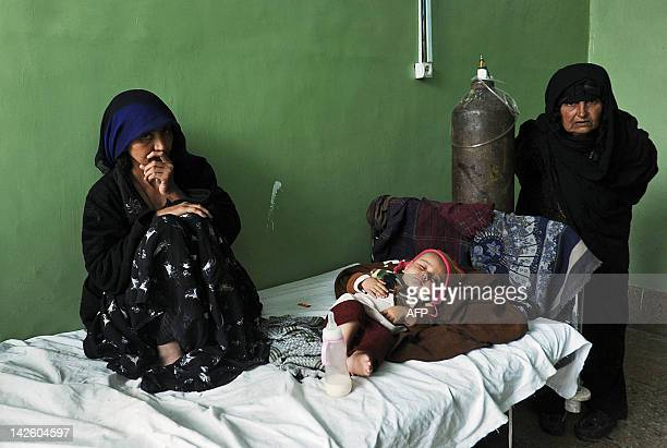 Afghan women look on as a child lies on a bed in a tuberculosis section of the main hospital in Herat on April 9 2012 According to the last estimate...