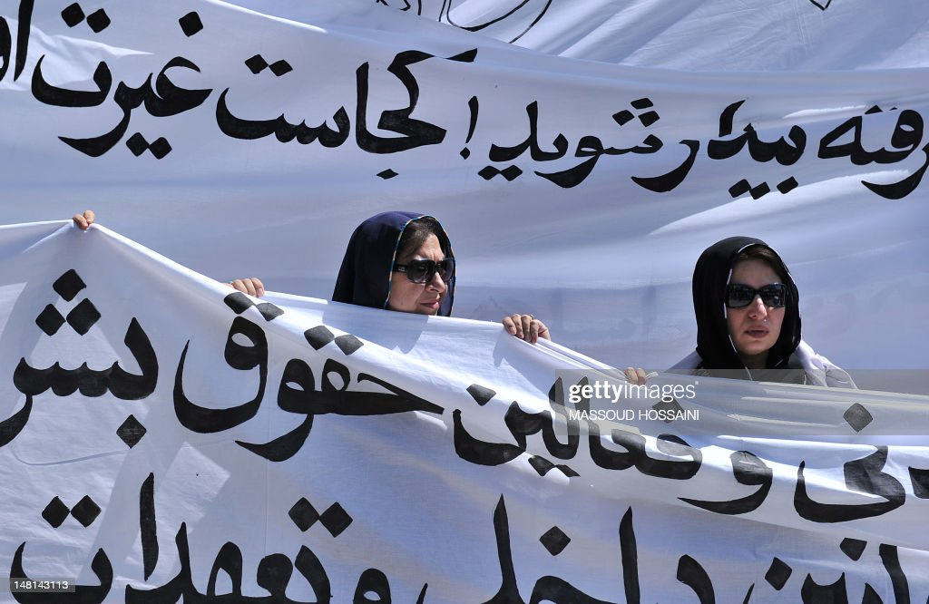 Afghan women march with banners to protest the recent public execution of a young woman for alleged adultery, in Kabul on July 11, 2012. Dozens of Afghan women's rights activists took to the streets July 11 to protest the recent public execution of a young woman for alleged adultery, which was captured in ahorrific video. AFP PHOTO/Massoud HOSSAINI