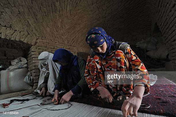 Afghan women of Turkmen ethnicity weave a rug in the Balkh province village of Siah Gerd on March 10, 2012. Mazar-i Sharif, which means respected...
