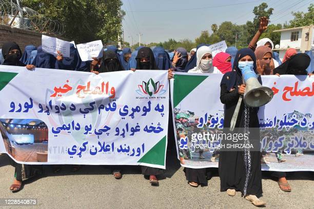 Afghan women protesters hold banners and chant slogans during a march to show their support towards peace talks between Afghan government and the...