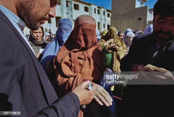 Afghan women, some dressed in niqabs, others in hijabs, with one woman holding her hand out to be marked by a man holding a pen at an unspecified...