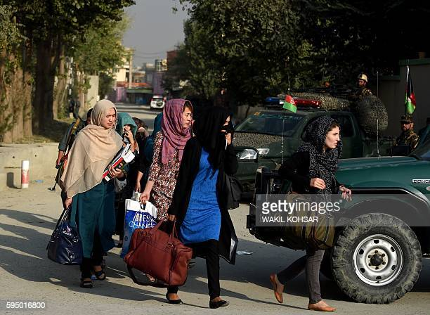 Afghan women students from the American University who were trapped inside the premises during an attack by militants are escorted by Afghan police...