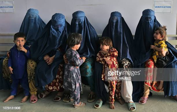 Afghan women wait during the visit of the United Nations High Commissioner for Refugees Filippo Grandi at the Azakhel Voluntary Repatriation Centre...