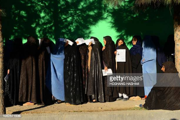 TOPSHOT Afghan women wait in line to vote at a polling centre for the country's legislative election in Herat province on October 20 2018 Afghans are...