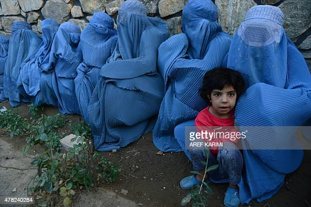 Afghan women wait with a child to get food from distribution scheme held during Ramadan in Herat on June 23 2015 Across the Muslim world the faithful...