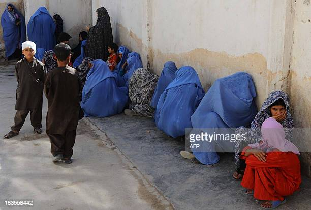 Afghan women wait with their children for a polio vaccination on the first day of a vaccination campaign in Herat on October 6 2013 A new threeday...