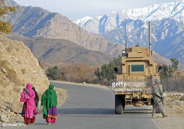Afghan women walk past US soldiers from 277 Field Artillery MPs 359th Steel Warriors on patrol in Nuristan Province on December 18 2009 US President...