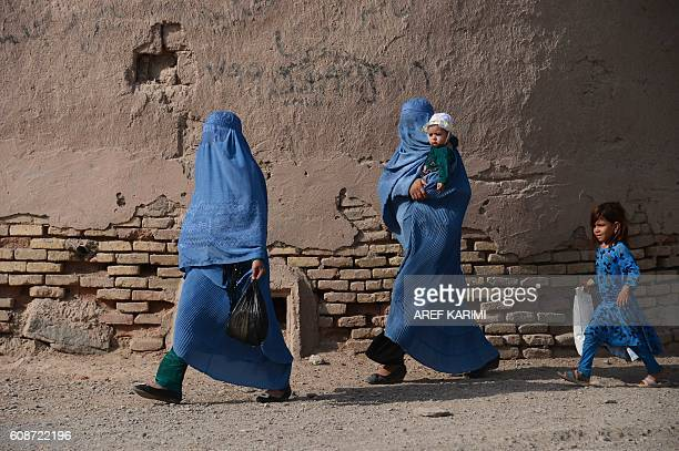 TOPSHOT Afghan women walk with their children through the old quarters of Herat on September 20 2016 / AFP / AREF KARIMI