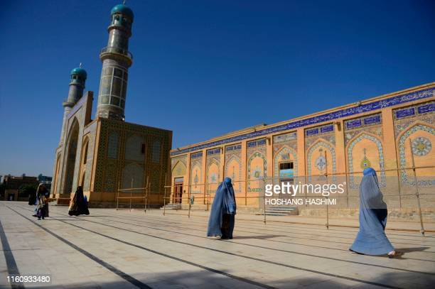 Afghan women wearing a burqa walk after Eid al-Adha prayers at the courtyard of the Jami mosque in Herat on August 11, 2019. - Afghans have started...