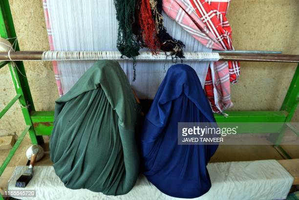 Afghan women wearing a burqa weave a carpet in a home in Kandahar province on July 14 2019