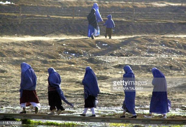 Afghan women wearing burkas walk on a foot bridge in central Kabul 04 Feburary 2003 While the burka is a reflection of deeply religious and...