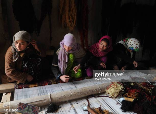 Afghan women weave a rug in Mazari Sharif on January 12 2012 Mazari Sharif is the capital of Balkh province with an existence of multiethnic groups...