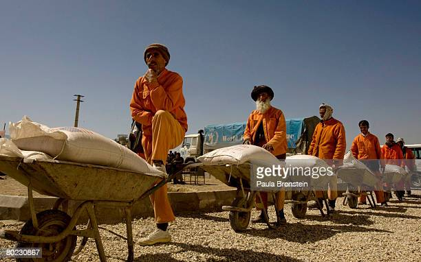 Afghan workers line up to deliver 100kg bags of wheat to Afghans in need during a World Food Program food distribution event on March 13 2008 in...