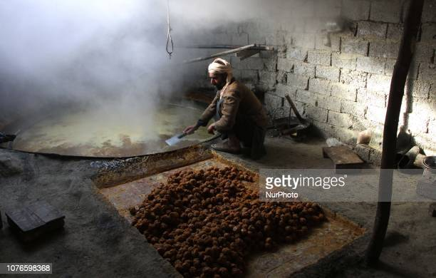 Afghan workers prepare brown sugar from sugarcane juice at a traditional factory in the Kama District of Nangarhar Province, east of Jalalabad, on...